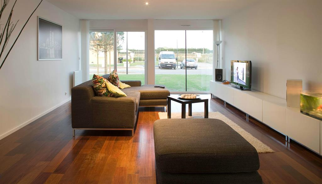 Salon avec canapé d'angle et banquette CG Architectes