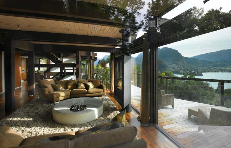 Salon classique avec chemin e centrale d 39 une villa luxueuse en ossature bois for Photo salon avec cheminee moderne