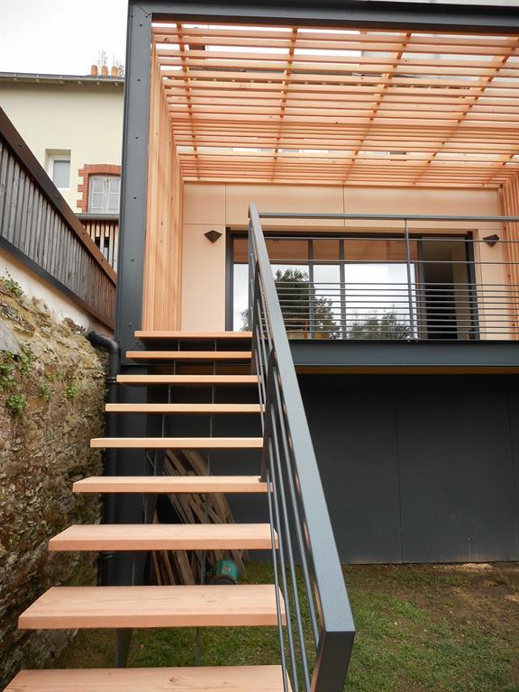 Extension avec pergola design en bois et aluminium abritant la terrasse for Pergola design alu