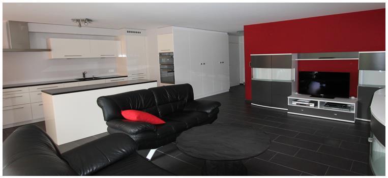 Constructeur Maison Moderne Bois : La cuisine blanche ouvre sur le salon moderne avec mur daccent rouge