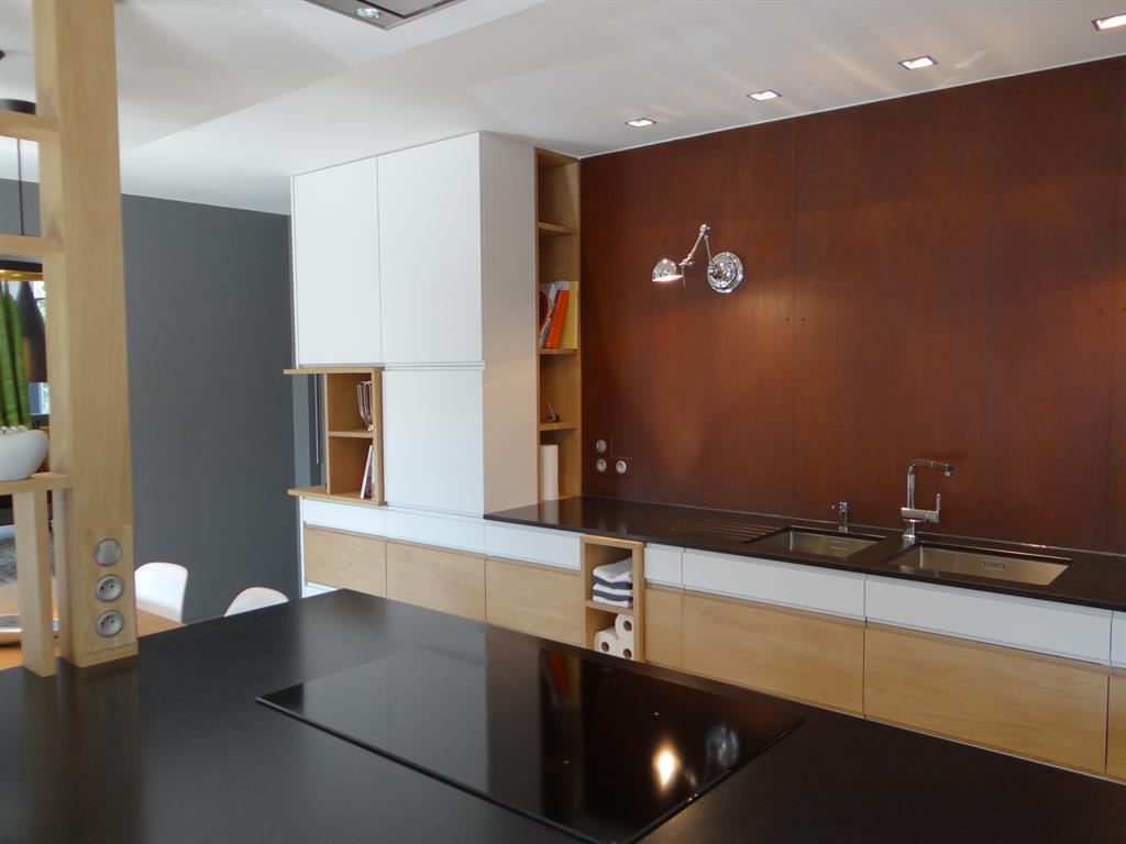 Cuisine contemporaine avec niches en bois et mur rouillé