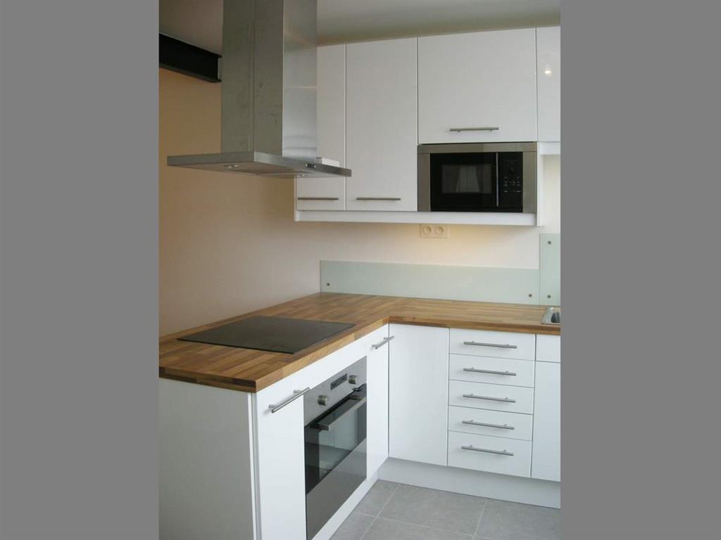 Cette petite cuisine ouverte laquée blanche avec son plan de travail