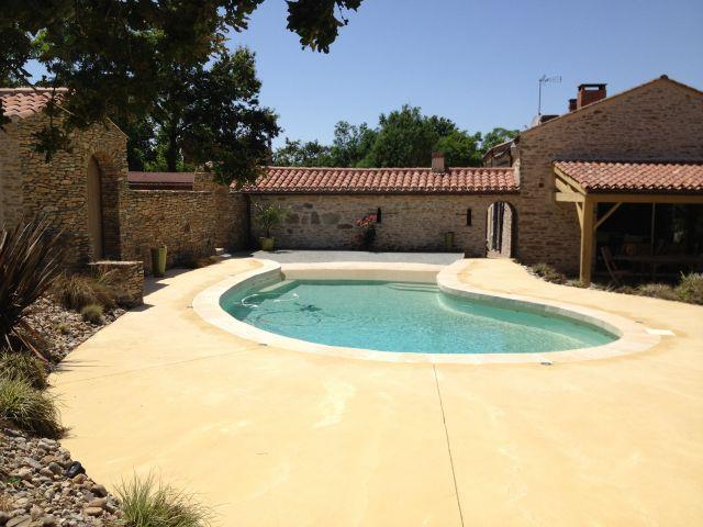 Piscine en courbe avec le bord couleur sable pour une for Sable piscine