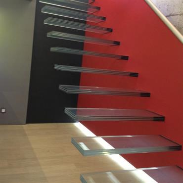 Dématérialisation de l'escalier par l'utilisation du verre. Marches encastrées dans le mur