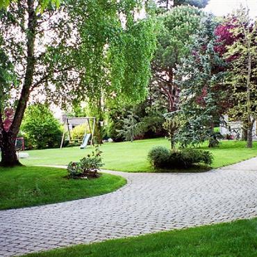 Jardin structuré par une allée en pavés blancs