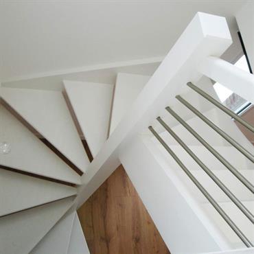 Cet escalier tournant suspendu en bois blanc est ajouré pour apporter transparence et légèreté