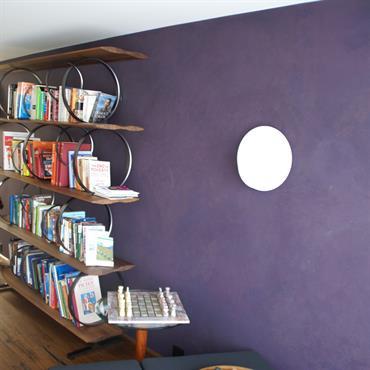 Bibliothèque création en bois et anneaux de métal posée contre un mur aux tons violets lumineux dans un esprit très déco.