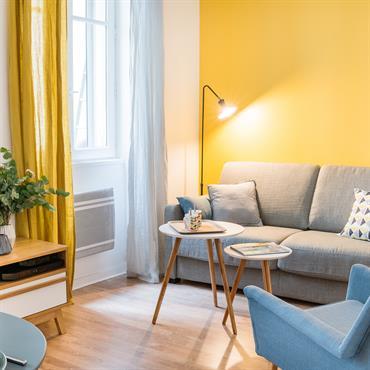 Salon coin canapé avec un grand mur jaune moutarde