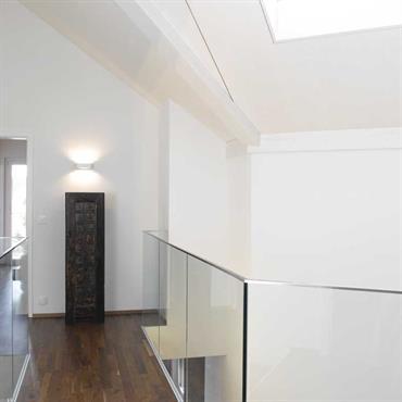 Passage en mezzanine lumineux. Ouverture zénithale, murs blancs, parquet foncé.