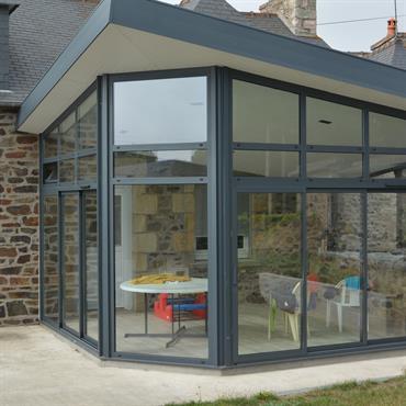 Extension d'une habitation avec un toit plat et une baie vitrée