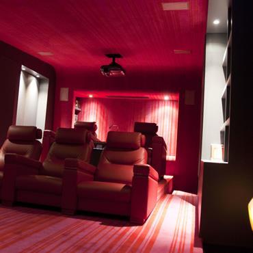 Home cinéma avec confortables fauteuils en cuir rouge. Murs et plafond tapissés de moquette rouge.