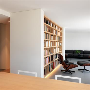 Salon de lecture lumineux avec grande bibliothèque.