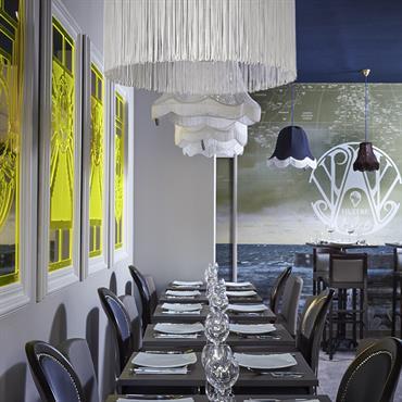 Salle du restaurant décorée par la décoratrice Soraya Deffar avec un panneau panoramique et les suspensions de Mitri Hourani de Boboboom
