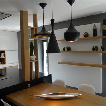 Dans cette cuisine contemporaine, le blanc, le noir et le bois créent une ambiance chaleureuse