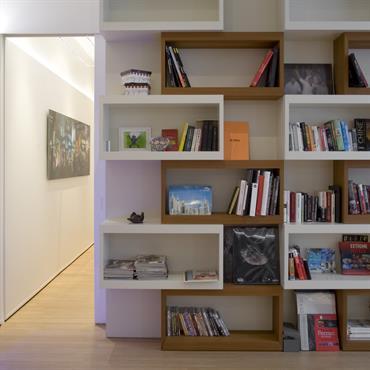 Bibliothèque sur mesure avec volumes géométriques blancs et bois.