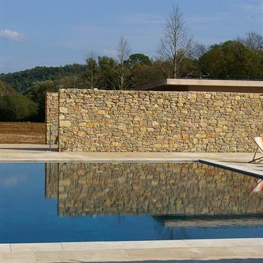 Piscine avec murs en pierre et terrasse dallée