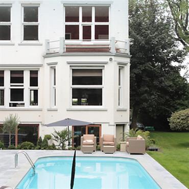 Maison blanche avec piscine et pelouse tondue.