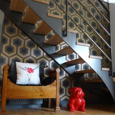 Le papier peint géométrique donne un coté design et original à cette cage d'escalier