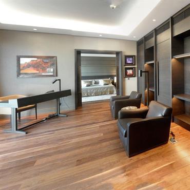Vaste bureau ouvert sur la chambre. Joint creux pour une lumière artificielle diffuse. Meuble bureau en bois massif teinté noir.