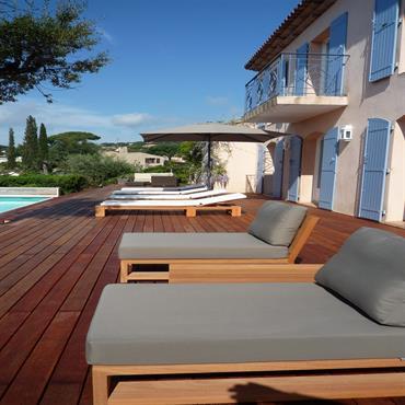 Grande terrasse en plein air au bord de la piscine d'une maison à la campagne.