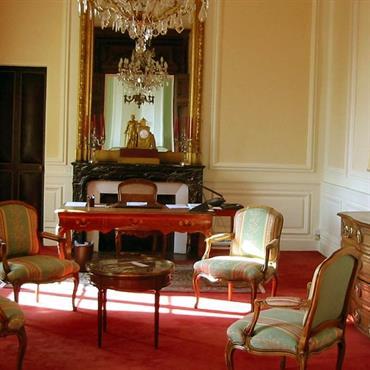 Bureau classique avec meubles anciens, soubassement menuisé, moulures et moquette rouge.
