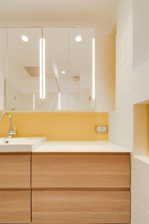 Petite salle de bain jaune et blanche avec meuble sous vasque