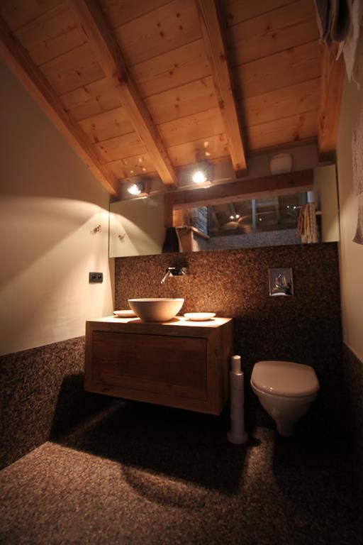Salle de bain avec WC, mosaïque grise, meuble suspendu en bois, poutres apparentes.