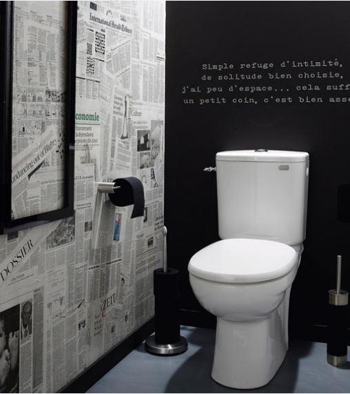 Toilettes avec un mur papier journal et un mur noir de type ardoise