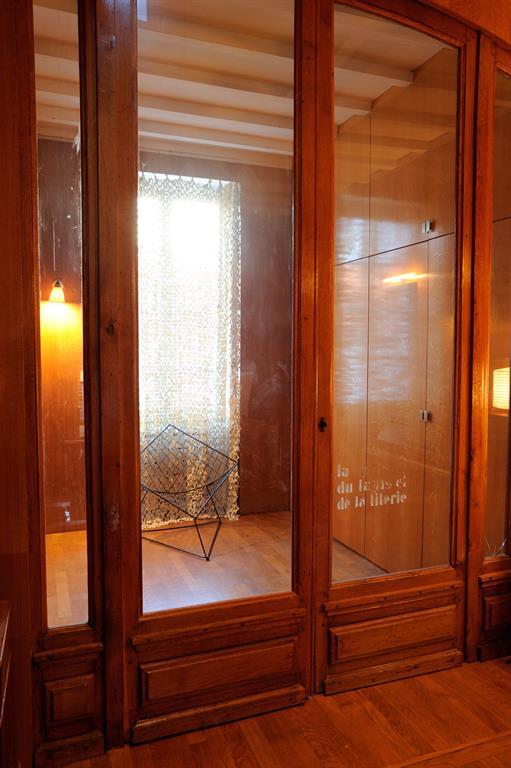 Grand dressing en bois derrière porte vitrée