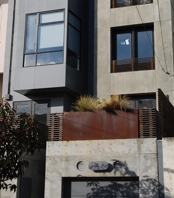 La jardinière en acier s'intègre parfaitement au béton des murs extérieurs