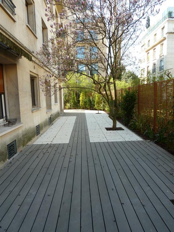 Image Terrasse en bois composite gris encastrées dans un dallage clair