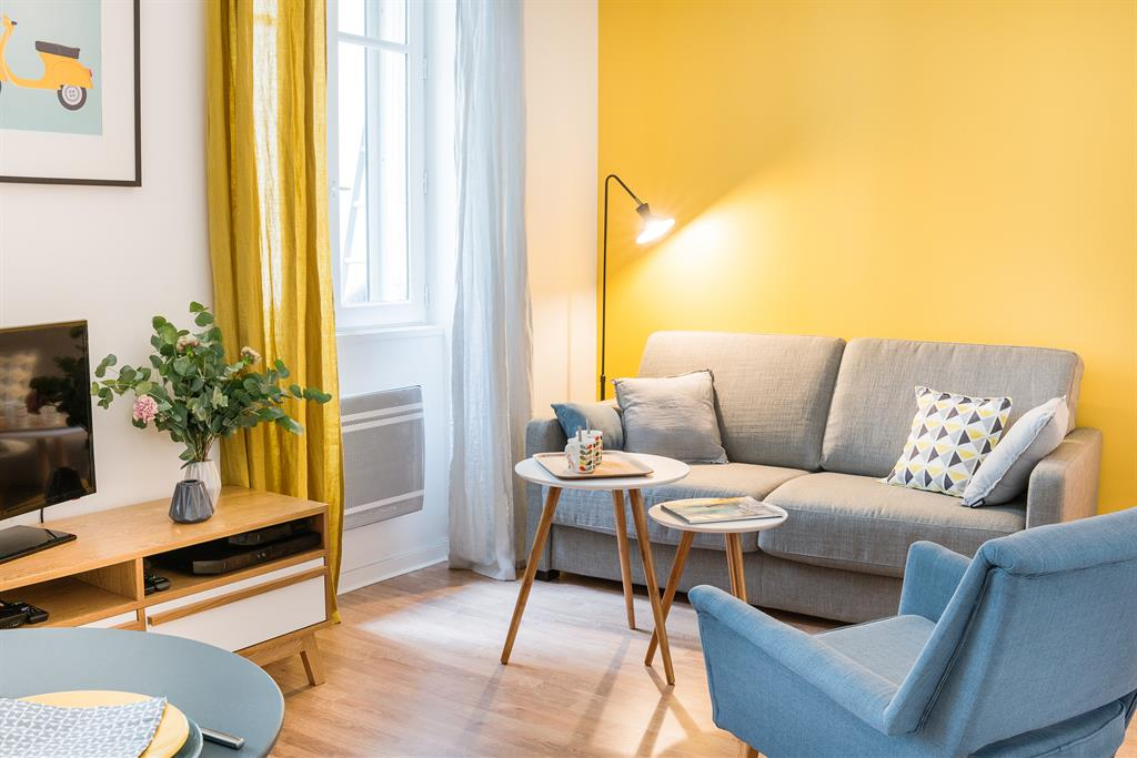 Salon coin canap avec un grand mur jaune moutarde for Petit salon contemporain