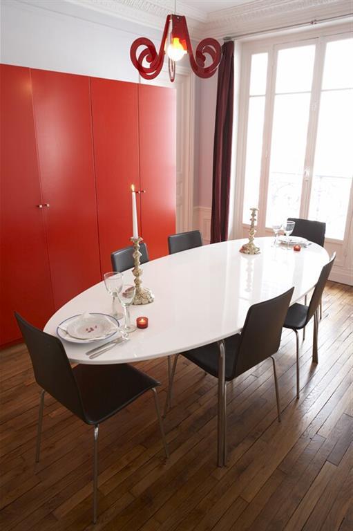 Salle à manger avec table ovale moderne et grand rangement rouge