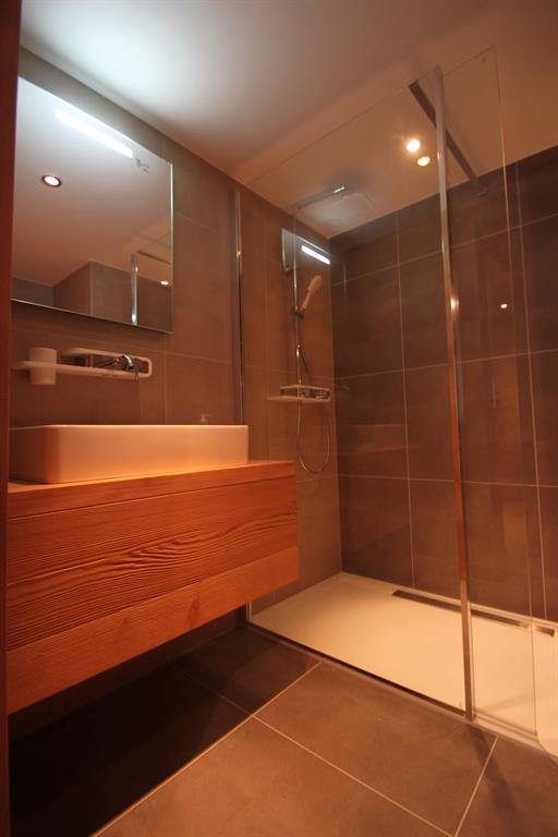 Salle de bain, grandes dalles de carrelage et meuble en bois massif.
