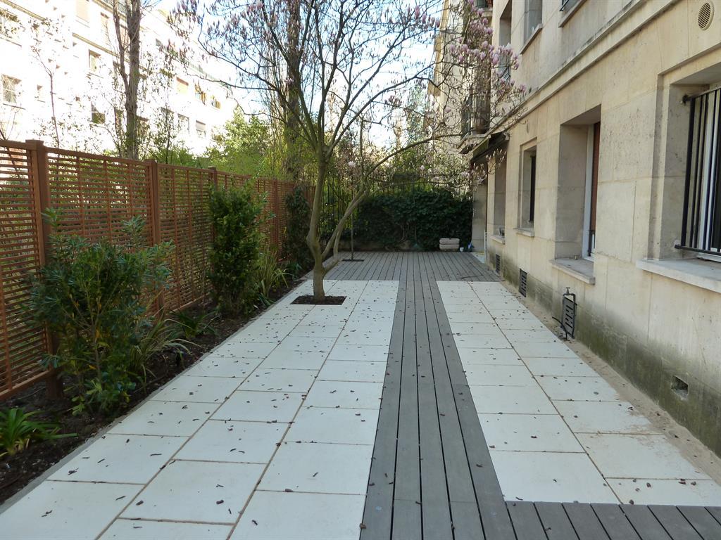 Terrasse en bois composite gris encastrées dans un dallage clair. Des palissades en bois exotique permettent de masquer le vis à vis. Une bande de terre permet de végétaliser l'aménagement. ...