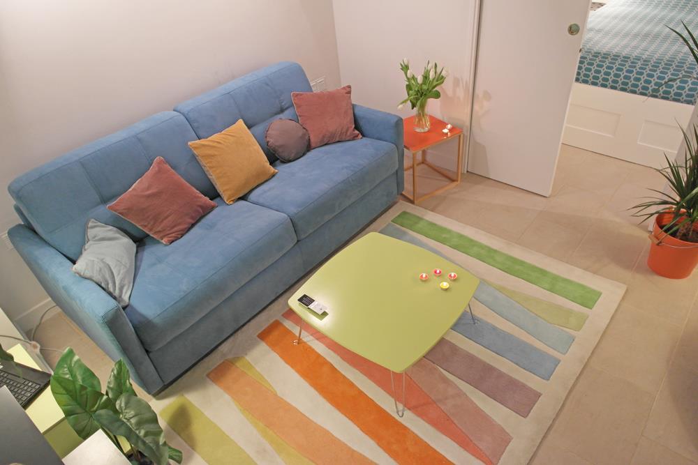Salon avec canapé bleu pastel et tapis coloré pastel