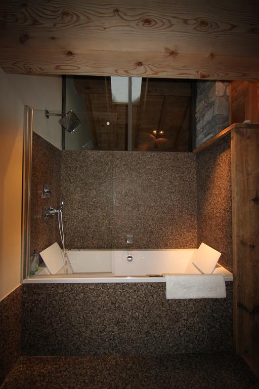 Salle de bain lumière tamisée. Mosaïque grise, bois et pierres