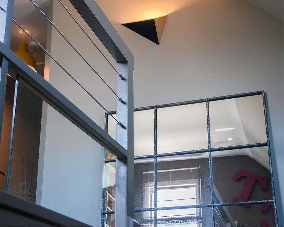 Montée d'escalier avec reflet dans le miroir industriel des lettres d'enseignes