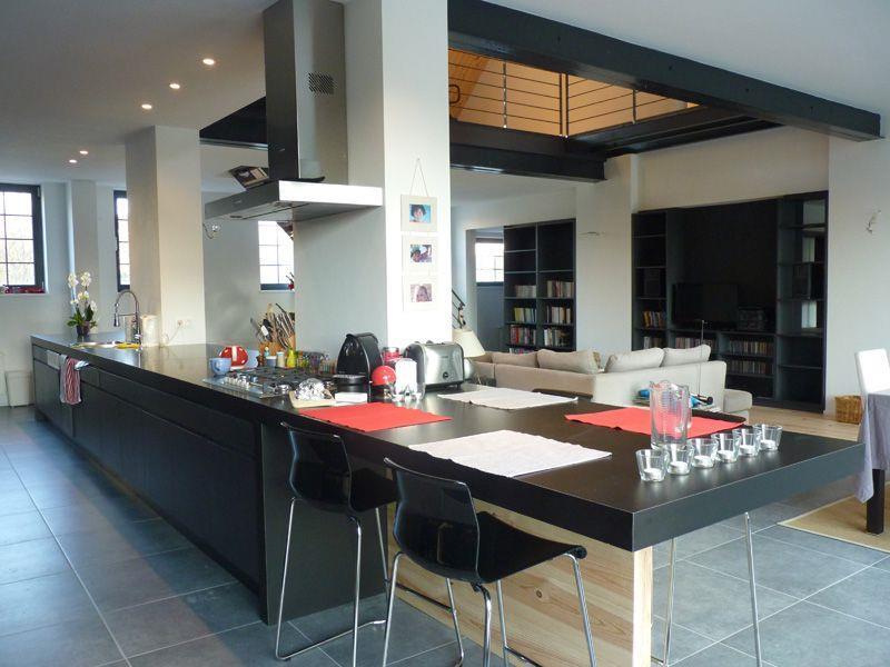 Cuisine moderne avec meubles en bois noir et grand plan de travail
