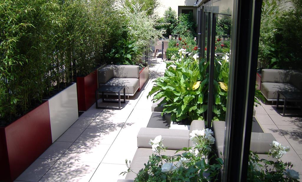 Salon d'extérieur entouré de plantes sur un balcon