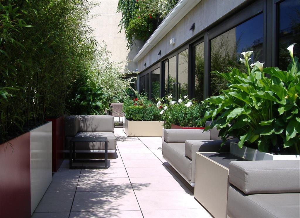 Terrasse aménagée avec végétation luxuriante en jardinières