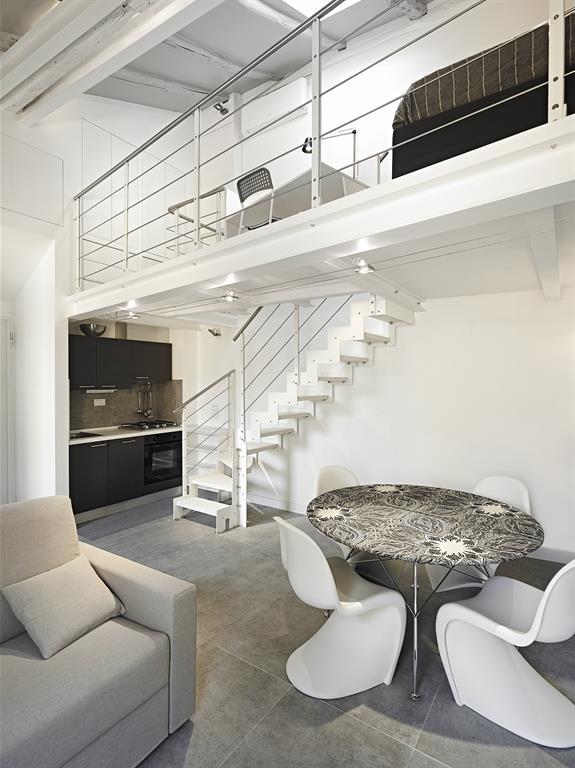 Pièce à vivre blanche avec chambre-mezzanine