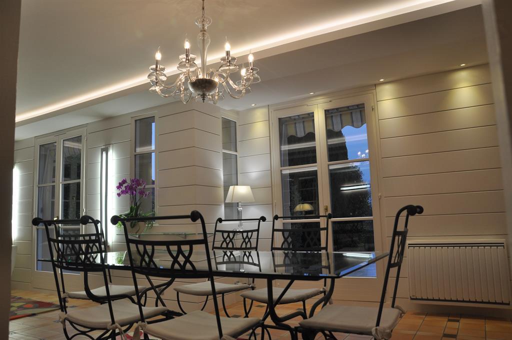 Salle a manger. mobilier néo-classique en métal patiné. Faux plafond avec corniche éclairée. Habillage mural en bandes horizontales