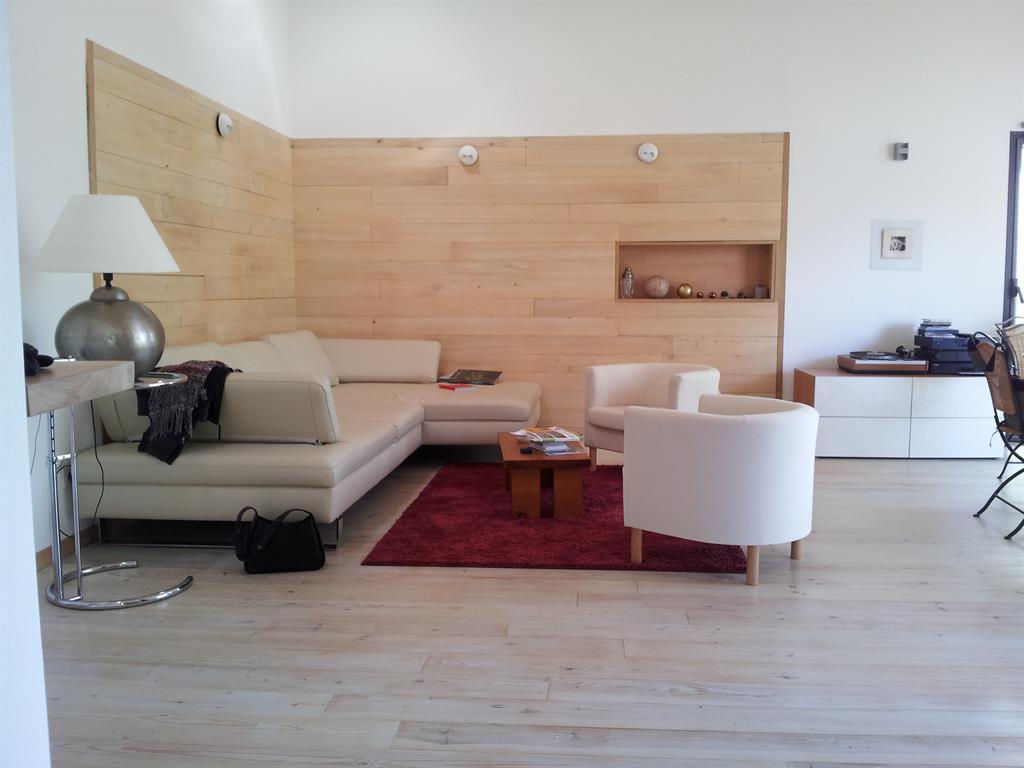 Murs avec placage bois et niche encastrée pour ce grand salon ...