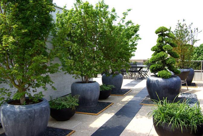 Jardin terrasse avec pots en pierres noires folia paysagiste for Salon de jardin moderne design