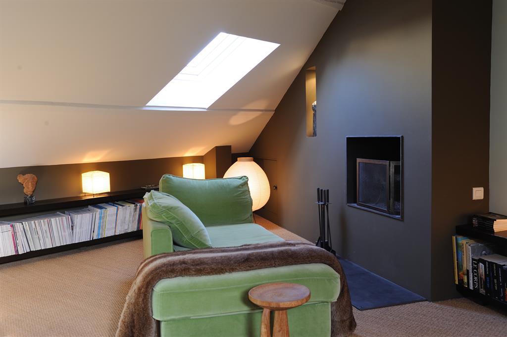Aménagement des combles en salon avec cheminée moderne encastrée