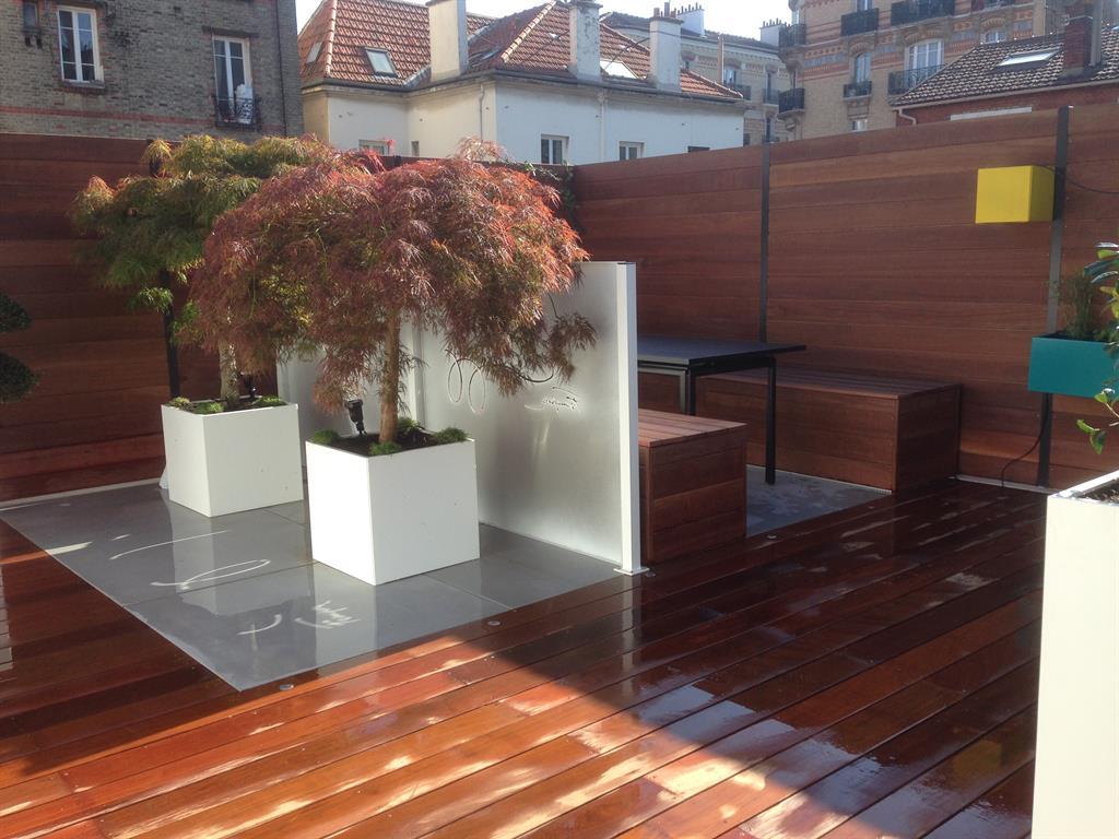 Terrasse 2 matériaux : dalles de béton teinté et lames de padouk. Bardage en bois exotique et palissades en aluminium sur mesure thermolaquées avec découpe laser. Banc coffre en bois ...