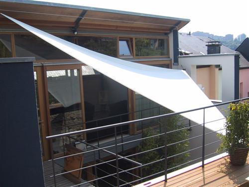 Voile d'ombrage installé pour protéger les espaces vitrés fortement ensoleillés