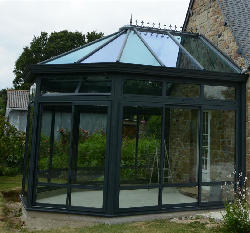 Véranda classique grise avec une toiture en verre vue de côté