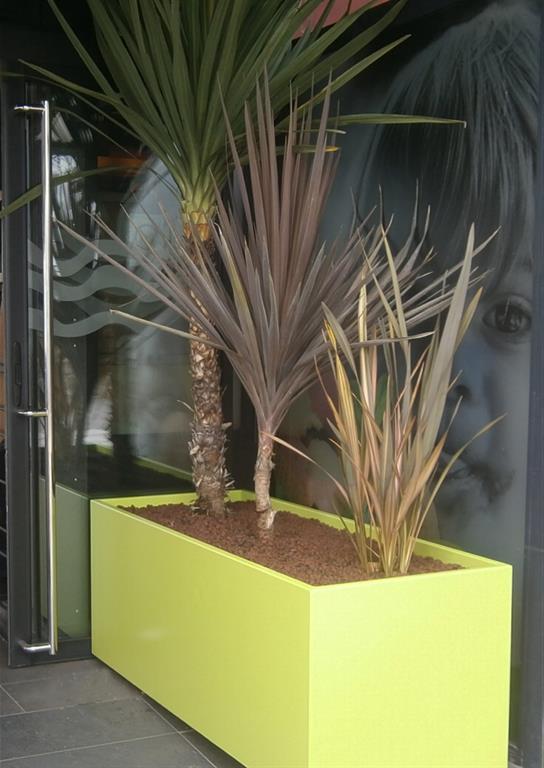 Bac à plante jaune-vert sur roulettes dissimulées